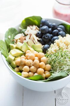 Spring Superfood Bowl with Blueberry-Ginger Dressing - a bed of fresh greens is topped with blueberries, quinoa, sprouts, chickpeas, avocado, almonds and blueberry-ginger dressing!