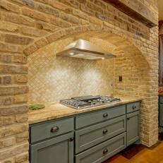 Neutral Brick Stove Area With Blue Cabinets & Stainless Steel Cooktop