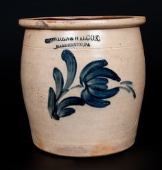 """$230.00 One-Gallon Stoneware Cream Jar with Cobalt Floral Decoration, Stamped """"COWDEN & WILCOX / HARRISBURG, PA,"""" circa 1865, ovoid jar with tooled shoulder and flattened rim, decorated with a brushed spitting tulip. Cobalt highlight to maker's mark. Excellent color. One chip to exterior of rim, a very minor chip to top of rim, and a tiny rim nick."""
