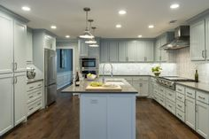 To update this beautiful kitchen, stainless steel appliances were added, a modern complement to the gray, Shaker-style cabinets. The trio of pendant lights are a focal point of the new, larger space and create friendly, ambient lighting.