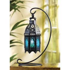 Candle light glimmers through lacy designs, turned into sapphire rays of light. This graceful hanging tabletop lantern enchants your home with the magic of a desert night!