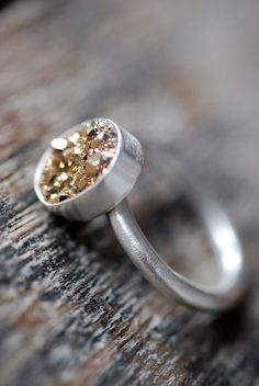 Gold dusty quartz set inside a silver setting. Easy peasy! I would raise it up a little.