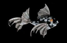 A Carved Snowflake Obsidian Fish, consisting of a carved snowflake obsidian body accented with fluted silver tone fins and inset orange ha