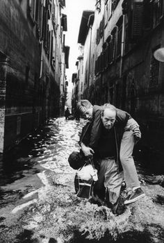 A man rescuing a boy on a flooded street of Florence. Florence, November 1966 MONDADORI PORTFOLIO/Giorgio Lotti