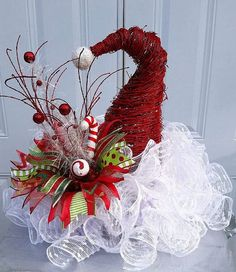 Heres a great idea for an addition to your Christmas Decor. This whimsical and unique Santa Hat Table Arrangement will be a favorite of everyone, including your guests. Use it as a centerpiece or as an accent on your sofa table, an occasional table, or on a table in your entryway. This would also be a great gift for someone special! It is approx 20 wide and 14-16 tall. Made with lots of beautiful Snow Ball Mesh ruffles and embellished with gorgeous ribbon and picks, this centerpiece is sure…