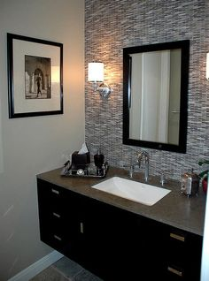 I like the lights, floating sink, and tile on the wall. The silver and black would also look nice with some red accents. This is more of a manly bathroom.
