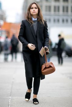 A long black coat paired with cap-toe flats.
