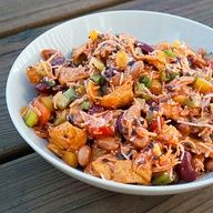 Tex-Mex Frito Salad 1-14.5 oz can red kidney beans  1-14.5 oz can pinto beans, rinsed  drained 10.5 oz-1 dry pint grape tomatoes, halved or quartered depending on their size 1/2-4.25 oz can of chopped olives 1 yellow pepper, diced 4 green onions, diced 1 c celery, chopped 2/3 of a 16 oz. Catalina Dressing 2 1/2 c finely shredded Mexican blend cheese 1-10.5 oz bag of Chili Cheese Fritos