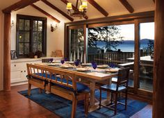 The dining area off the great room utilizes a built-in banquette to store table settings; an antique Irish bench and English chairs surround the cerused-oak dining table; the patchwork Persian rug was dyed a deep cobalt.