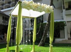 Wrap the chuppah legs in a pretty green, and stretch white across the top with curtain tie-backs around the sude.