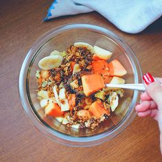 """Tropical fruits breakfast bowl: banana, pineapple, apple, papaya with crunchy granola bits, cacao nibs and propolis honey. So fresh"