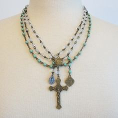 "Three Strand Cross Necklace  Three delicate strands of beads all strung with eye hook chain for more detail. One large crucifix with two smaller saint medallions. One strand of mint green color beads and two clear. Adjustable lobster claw clasp.  19"" long with 2"" cross"