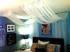 Partial Canopy. Create one single panel instead of the two separate ones pictured. Also use curtain rods to hang them (paint to match the fabric if necessary). This may be a good idea for a way to really spruce up the room while keeping with apartment living.