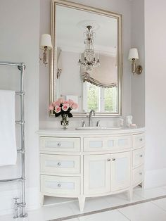 Go beyond the bathroom section of stores to look for your mirrors. Often mirrors intended for living rooms work perfectly in a bathroom and have more interesting details and style. Add a little impact with a glam chandelier.