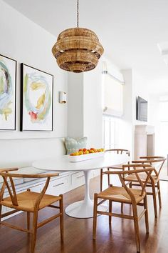Clean breakfast nook is filled with a 3-tier woven basket chandelier illuminating an oval Saarinen Dining Table lined with 4 Hans Wegner Wishbone Chairs as well as a long built-in bench fitted with drawers tucked under side by side pastel colored abstract art pieces.