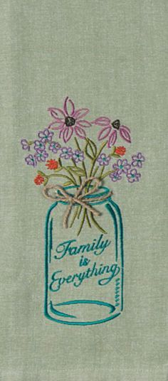 "Embroidered Chambray Tea Towel with Mason Jar Design. Embroidery saying: ""Family is Everything"". Appliqued top and twine bow accent. Color: Green, 100% Cotton"