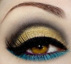 Gold eyeshadow on lid with smokey gray above and black eyeliner in a sweeping pattern. Purple eyeliner on the bottom inside and a turquoise eyeliner under the bottom eyelashes. Finish off with a coat of very black mascara.