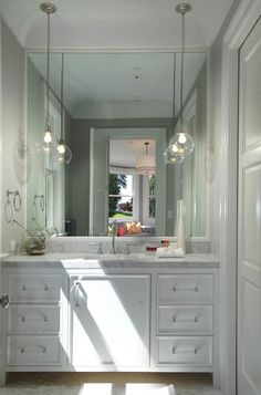Chic bathroom with a white built-in sink vanity paired with lucite pulls along with undermount sink and gooseneck faucet framed by marble countertops.
