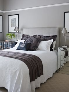 Mismatched bedside tables, grey headboard. Note use of grey walls