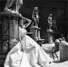 Dorian Leigh, is a strapless evening gown by Giovannelli-Sciara for Haper's Bazaar, The Coliseum, Rome, 1952