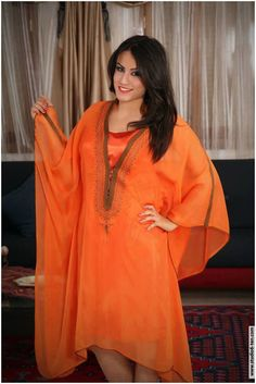 Woman in a modern dress of rich orange color. The cut of the dress and the embroidery pattern on the front part are typically Tunisian