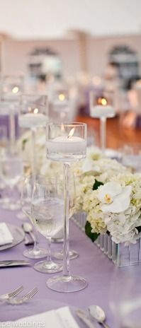 Lavender linens and candles with a mirrored silver box container filled with hydrangeas and orchids at Mount Hope Farm