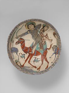 Two scenes of Bahram Gur and Azada Object Name: Bowl Date: 12th–13th century Geography: Iran, Kashan Medium: Stonepaste; polychrome in-glaze and overglaze painted and gilded on opaque monochrome glaze (mina'i) Dimensions: H. 3 7/16 in. (8.7 cm) D: 8 11/16 in. (22.1 cm) Diam. 8 11/16 in. (22.1 cm) Classification: Ceramics