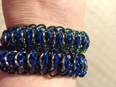 "2 viperscale bracelets done with twisted square wire 5/16"" aa rings.  Top - black/blue/green Bottom - black/gunmetal/blue"