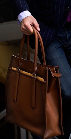 Handsomely burnished leather and beveled strap anchors give the modern Legacy Leather Tote a timeless Coach look.