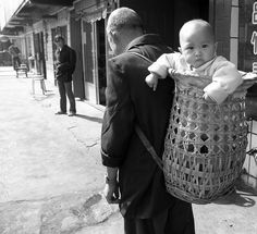 Traditional Chinese babywearing. I kinda love this. The basket must be super lightweight and the baby has freedom of movement.