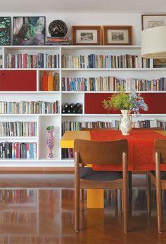 """Bagunça longe dos olhos: Quando o casal precisou transformar o escritório em quarto para Dora, a sala de jantar virou espaço de trabalho. """"Escondemos a bagunça de cada um em dois nichos compridos da estante, fechados com as portas vermelhas"""""""