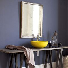 Adorable bathroom. Muted blue-gray wall and a vibrant yellow vessel sink.