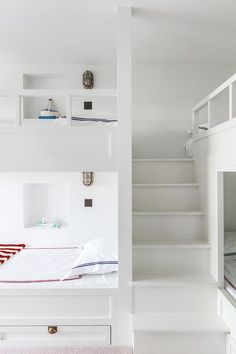 White built-in cottage bunk beds feature shaker drawers with antique brass cup pulls dressed with red and blue bedding.
