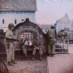 Two Americans of the 2nd Armored Division guarding German prisoners near the bridge over the Bega river in the town of Lemgo, North Rhine Westphalia, Germany. 4/5th April 1945.