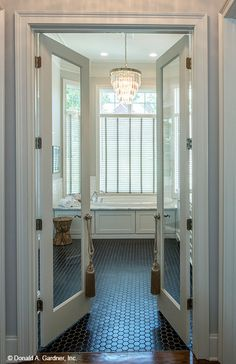 French doors create an elegant entry to this master bathroom. The Monarch Manor house plan 5040. #WeDesignDreams