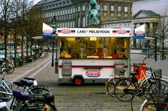 Danish Hot Dogs ~ Danes are crazy about their hot dogs. On nearly every Copenhagen corner, a pølsevogn, or hot dog wagon, offers more than a dozen varieties. The ristet, accented with sweet spices, gets tucked in a bun loaded with pickles, raw and crispy fried onions, and rémoulade; the medister is spiced with cloves and allspice; and the fransk makes ingenious use of a baguette-like roll, the bread hollowed out and used as an edible sleeve for the footlong frank. #Copenhagen #Hot_Dog…