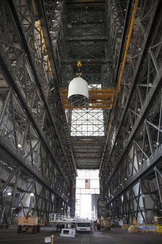 In the transfer aisle of the Vehicle Assembly Building at NASA's Kennedy Space Center in Florida, a crane operator lifts a full-size mock-up of the Orion spacecraft high in the air for transfer to High Bay 4. Image Credit: NASA/Dan Casper