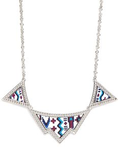 This stunning necklace takes the tribal trend to glittering, glamorous terrain. The delicate links and sparkling silver beads offer a glitzy counterpoint to the crafty and colorful Native American graphics.