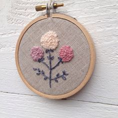 This simple but sweet embroidery design brings a beautiful touch of floral sweetness into any room.  In shades of mauve, lavender, and cream, this delicate flower is made out of tiny french knots hand stitched on to a natural linen. Perfect for a little girls room or tucked on to a shelf next to your favorite classic books, this is a hand embroidered treasure to keep for always.  ♡ Set in 3 wood hoop.  ♡ All of my hoops come finished with a wool felt backing.  ♡ Sized perfectly to display on…