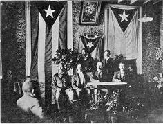 Primera foto donde aparece publicamente la bandera de Puerto Rico.Esta foto fue tomada en la capital de Jamaica, en el año 1892. Es de gran importancia histórica. La foto capta la reunión de los miembros del consejo de Kingston presidida por Jose Martí al centro, en su incansable lucha por la libertad política de nuestros países. Puerto Rico, estudiosos identifican esta antigua imagen como la primera foto donde aparece públicamente en la historia la bandera de Puerto Rico.