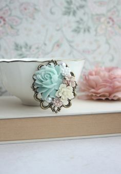 ♥´¨) ¸.•´ ¸.•*´¨) (¸.•´ ♥ ~ A beautiful antiqued bronze filigree flower collage brooch. A gorgeous selection of large to small flowers in shades of Mint green ivory, blush pink, faux pearl cabochons, and an oxidized brass leaf. It has a good weight and solid. A romantic and versatile piece for a special day, or to pin onto your jacket, sweater, scarf, wedding bouquet and cummerbund or sash.  This large brooch measures approximately 51 x 60mm. :: For beautiful and romantic hair accessories…