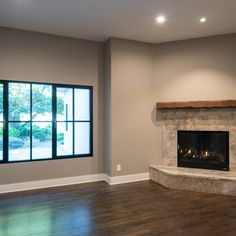 Den adjacent to main living room features live edge mantle and gas fire place. Recessed can lights as well as large windows help brighten up the space.