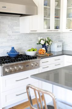 white shaker cabinets, some with glass inserts, bar pulls, mosaic backsplash, stainless steel appliances