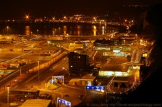"""Night Panorama of the Ferry Terminal and Eastern Docks of Dover Harbour, Kent, England, UK. A view of """"Space City"""" taken from edge of the White Ciffs of Dover below the Coastguard Station. Cross-English Channel ferry operators: P and O Ferries, DFDS Seaways (Norfolk Line), and MyFerryLink (ex-SeaFrance ships). Bottom: Booking Hall, Arrivals, Athol Terrace, Marine Parade. Top: Western Docks, Marina (Wellington Dock), and Seafront. Travel and Tourism. See…"""