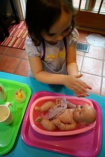 washing baby doll, skye usually does this in bath but how cute is that setup.