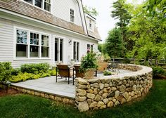 Cozy patio area features custom stone wall.  Yard Boss Landscape Design LLC Mattapoisett, MA