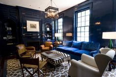 gloss blue walls, large ottoman, printed rug, traditional moldings, contemporary light fixture