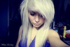 Platinum blonde scene hair; deep blue dress.