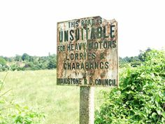 """Old sign, Busbridge Road, Loose by Chris Whippet, via Geograph. """"This road is unsuitable for heavy motors, lorries & charabancs by order Maidstone R. D. Council""""."""