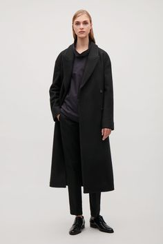 Fastened with hidden front buttons, this coat is made from soft wool with a matching fabric tie fastening around the waist. Slightly oversized, it has a crossover front, wide notched lapels and subtle in-seam pockets.